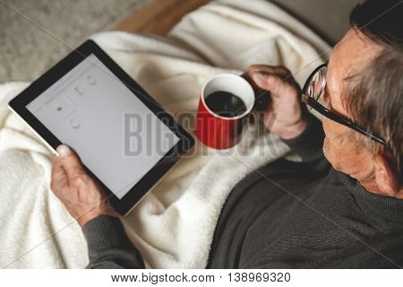 Senior with spectacled sitting on the couch with a tablet  and red cup of coffee in hands. Online education retirement concept. e-Learning. mock up