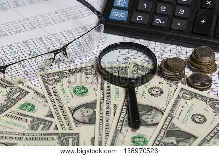 Business concept. Closeup of spectacles, dollar bills, calculator, magnifying glass and coins on paper with digits.