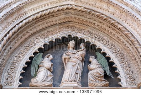 FLORENCE, ITALY - JUNE 05: Virgin and Child with Two Angels, Portal on the side-wall of Cattedrale di Santa Maria del Fiore (Cathedral of Saint Mary of the Flower), Florence, Italy on June 05, 2015