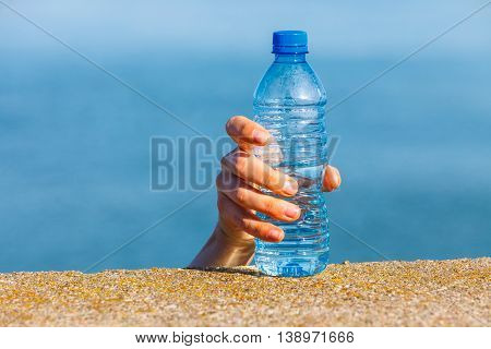 Male hand taking away water plastic bottle outdoor on sea shore