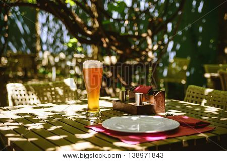 Glass of light beer on a table of street cafe