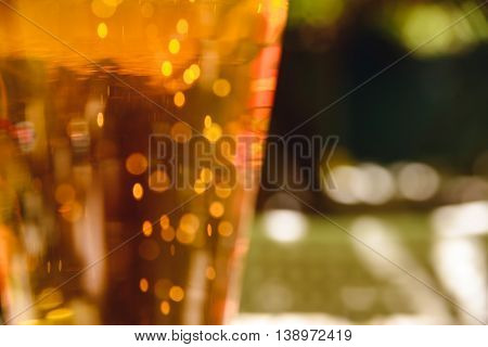 Close-up photo with glass of light beer and sparkles
