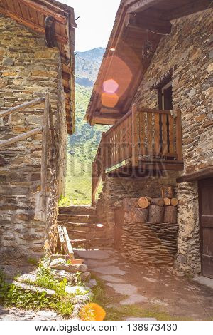 sun flare between stone chalet on Alps mountain