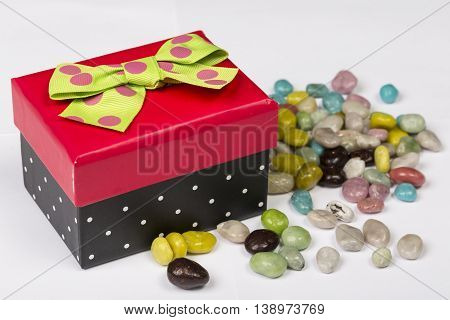 Funny red and black gift box with green ribbon with candies on white