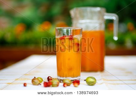 Orange drink is poured into a glass and decanter.