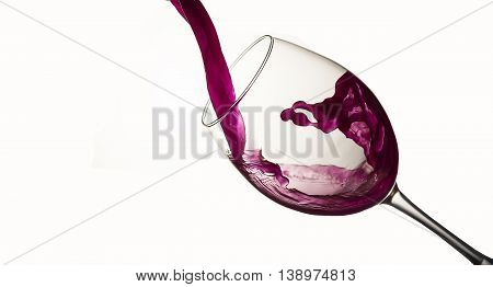 Red wine pouring in a wineglass on light background