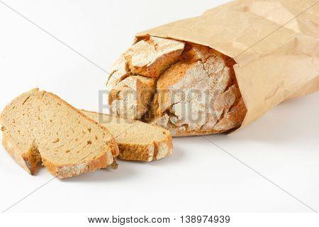 freshly baked loaf of bread in paper bag