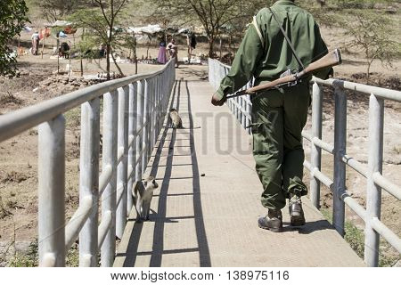 NAIROBI, KENYA-SEPTEMBER 10, 2014: An unidentified game warden walks along a bridge in Nairobi National Park, Kenya
