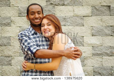 Interracial charming couple wearing casual clothes posing for camera and embracing in front of grey brick wall.