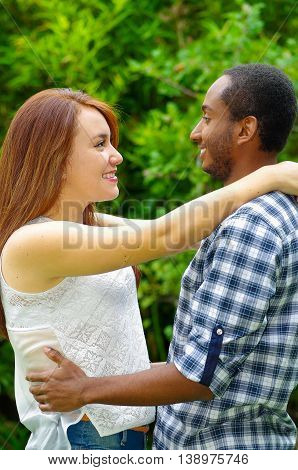 Interracial charming couple wearing casual clothes embracing and posing for camera in outdoors environment.