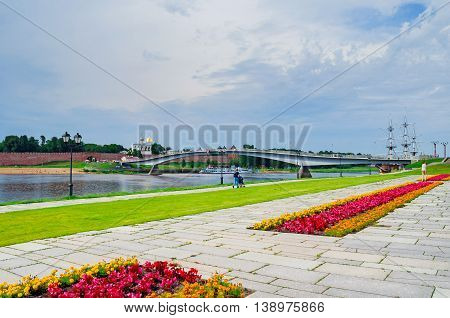 VELIKY NOVGOROD RUSSIA - JULY 15 2016. Novgorod Kremlin with footbridge and embankment near the Volkhov river in summer cloudy day - architecture city view. Selective focus at the Kremlin