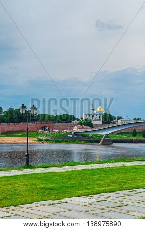 VELIKY NOVGOROD RUSSIA - JULY 15 2016. Novgorod Kremlin with footbridge and embankment near the Volkhov river in summer cloudy day - architecture landscape. Selective focus at the Kremlin