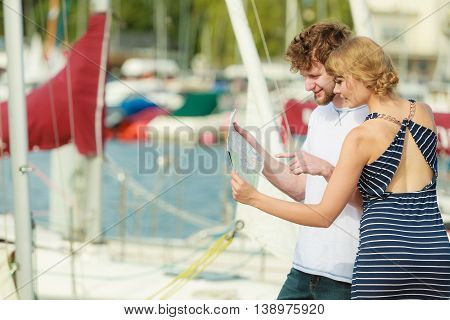 Summer travel concept. Young tourist couple on vacation standing in front of boats in marina looking up directions on map