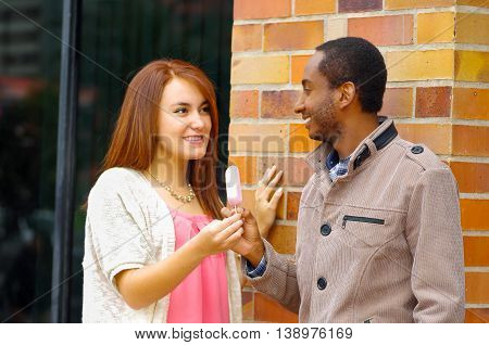 Interracial charming couple wearing casual clothes interacting happily and sharing an ice cream.