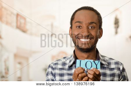 Headshot handsome man holding up small letters spelling the word joy and smiling to camera.