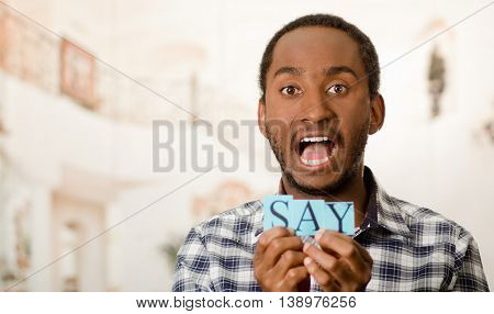 Headshot handsome man holding up small letters spelling the word say and showing dramatic facial expression to camera.