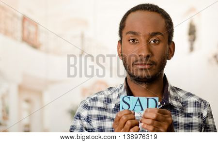 Headshot handsome man holding up small letters spelling the word sad and looking to camera.