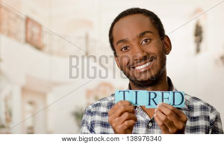 Headshot handsome man holding up small letters spelling the word tired and smiling to camera.