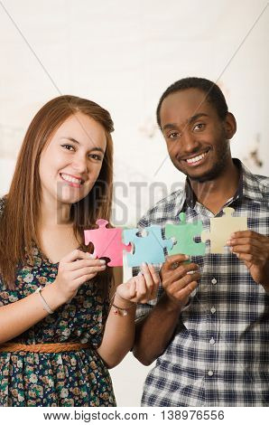 Interracial charming couple wearing casual clothes holding up large puzzle pieces and interacting happily, white studio background.
