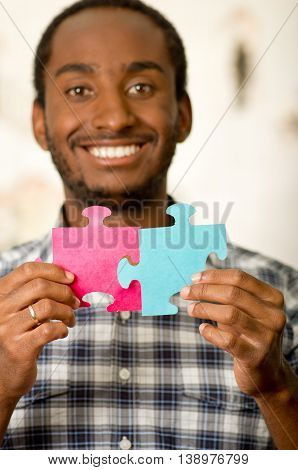 Headshot handsome man holding up big puzzle pieces in pink and blue, smiling happily to camera, white studio background.