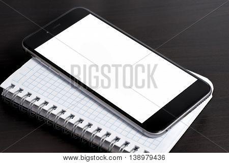 Smartphone and notepad on dark table .