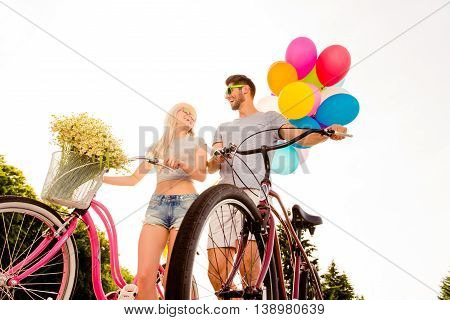 Two Happy Lovers Resting And Walking With Bikes And Balloons
