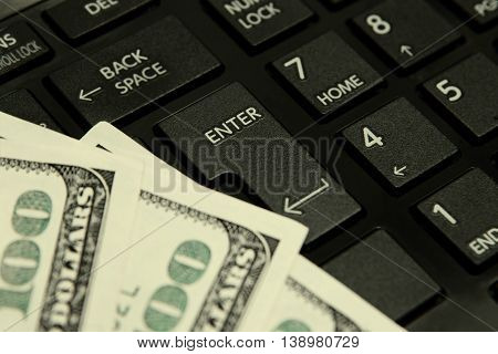 One hundred Paper dollar bill on computer keyboard