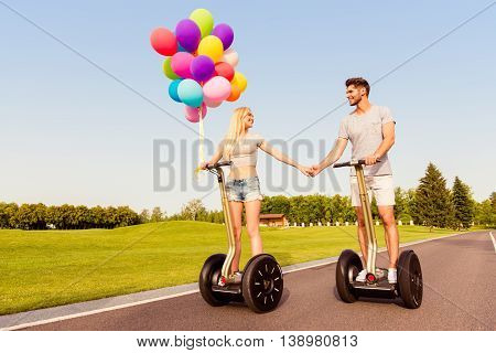 Young Cute Couple With Balloons Holding Hands  On Segways In Park