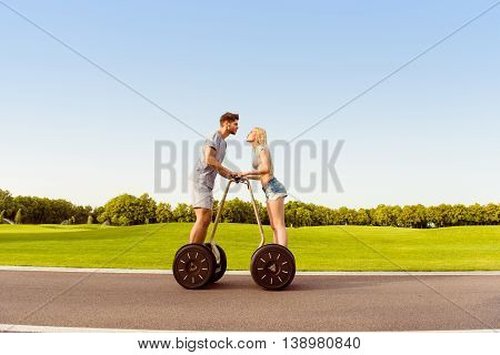 Romantic Couple In Love Standing On Segways And Going To Kiss