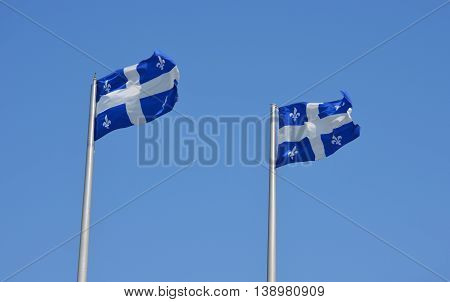 Quebec flags fluttering in blue sky in Montreal.