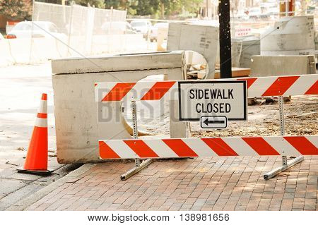 sidewalk road closed sign and traffic cone in the street