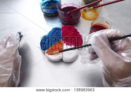 The men wearing gloves are painting on the fabric Fabric Tie-dye.