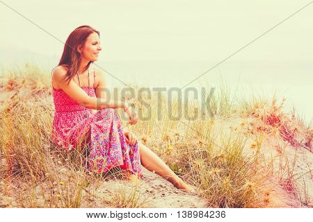 Woman sitting in sand at beach