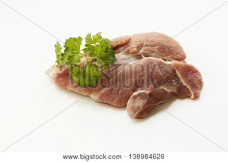 red raw meat piece with vegetables and greens on a white background