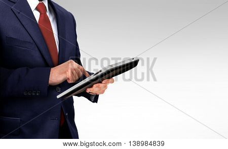 Business man holding digital touchpad over white