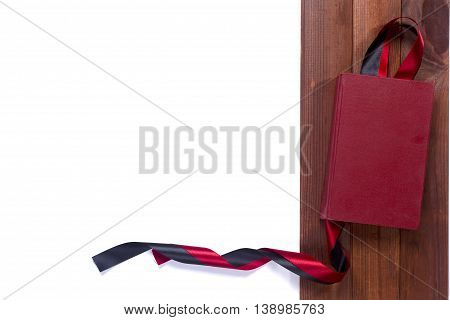 Black red satin ribbon and a book on a wooden background