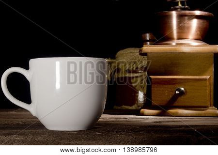 Cup of coffee and grinder on wooden table