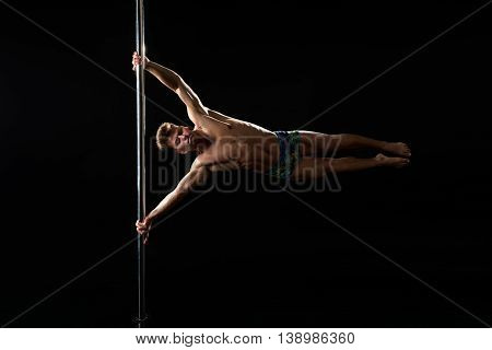 Male pole dance. Image of dancer with strained face