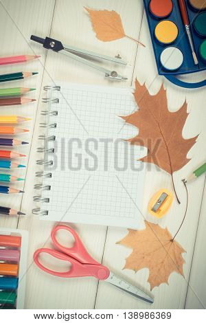 Vintage photo Office accessories and orange leaves on white boards copy space for text in notepad back to school in autumn concept