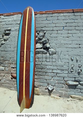 Longboard surfboard with blue and brown stripes leaning against wall at Surfrider Beach, Malibu.
