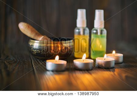 Burning candles and oil for aromatherapy and massage. Singing bowl on dark wooden background.