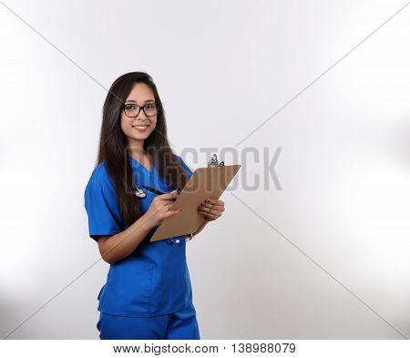 A young hispanic nurse in blue scrubs wearing glasses.