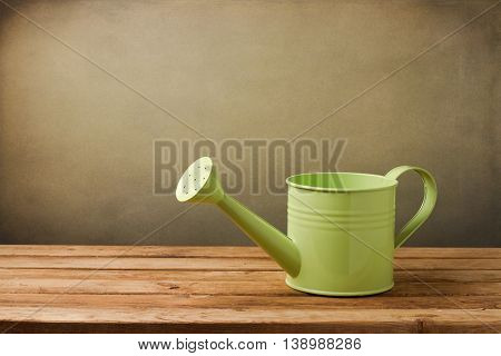 Water can on wooden deck table over grunge background