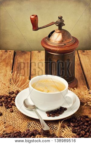 Vintage coffee grinder and coffee cup over wooden background
