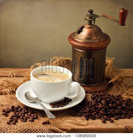 Coffee cup with vintage grinder on wooden table