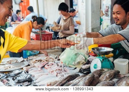 GEORGE TOWN MALAYSIA - MARCH 23: Man buys seafood at the local market of Penang on March 23 2016 in George Town Malaysia.
