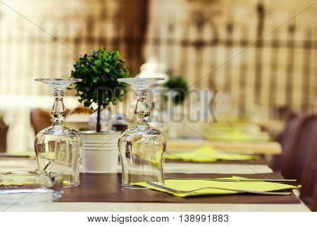 Street cafe table arrangement over blur fence background