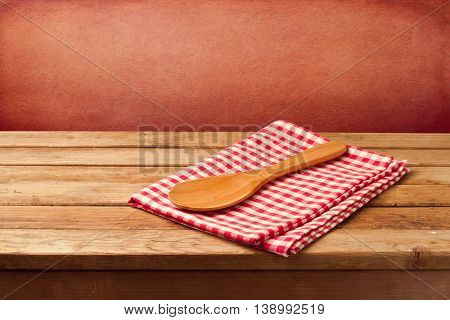 Wooden table with tablecloth and spoon over rough concrete wall