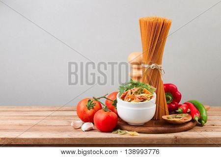 Whole wheat spaghetti and vegetables on wooden tabletop