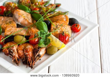 Greek cuisine - traditional grilled seafood plate with shrimps, salmon, olives lemon and cherry tomato on white wooden background